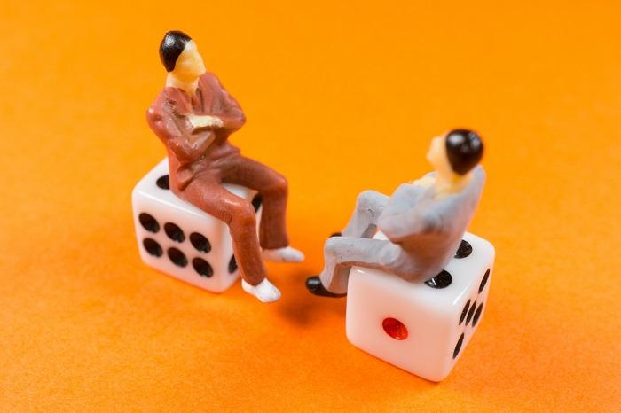 サイコロに座る男性