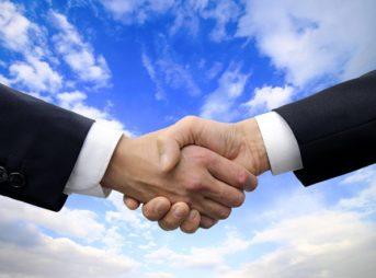 握手する手と空