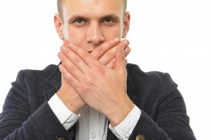 口を手で隠す男性