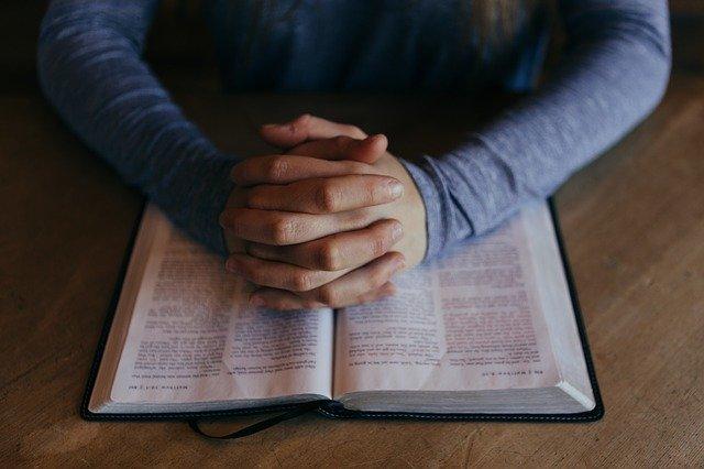 手を組んで祈る男性